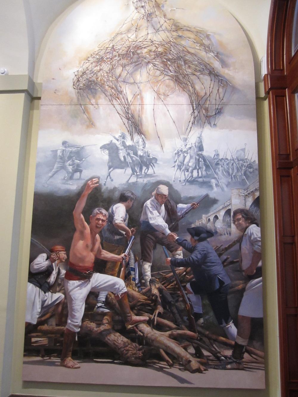 Este mural presenta una alegoría sobre la guerra de la Independencia y, al tiempo, refiere el arrebato del heroísmo.