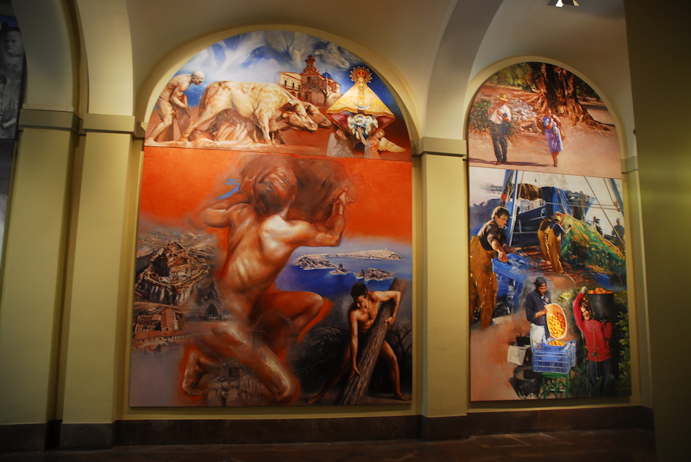 The third mural has got on the top the patron saint of the capital of the province, the Mother of God of the Lledó. On the inferior panel, there is a reference to the local mythologie of Castellón, in the powerful figures of Tombatossals and Arrancapins.  The primary sector: the painter focuses on three labour activities as the collected of the oranges, the fishing which takes up the middle of the painting and the rainfed agriculture.