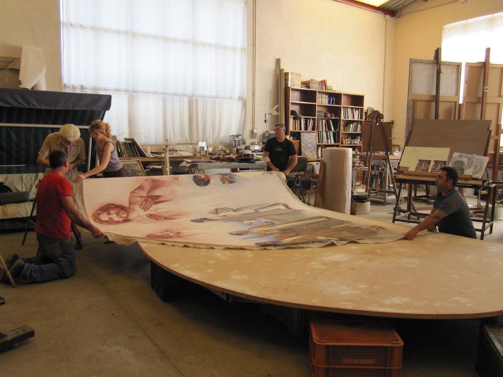 La tela se extrae del bastidor y se enrolla para poderla transportar y entrar en la Iglesia de Cabanes.